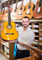 Guy choosing guitar in music shop.