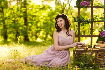 woman in elegance dress sits on the ground in the wood near decorations