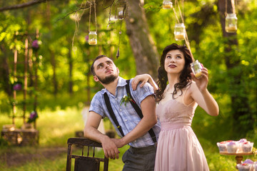 Old styled dressed bride and groom kiss near wedding decor zone