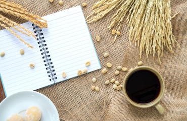 Coffee and sweets with notebook and pen on Sackcloth brown.