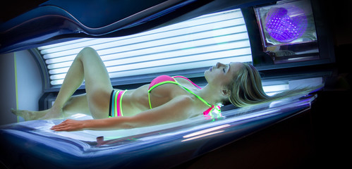 Beautiful young woman have tanning skin treatment in modern sola