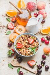 Healthy breakfast ingredients. Oat granola in bowl with nuts, strawberry and mint, milk in pitcher, honey in glass jar, fresh fruits, berries on light concrete background