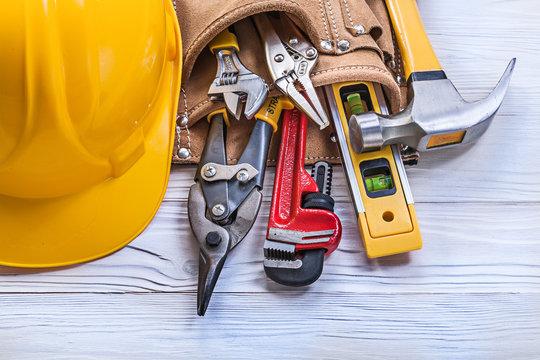 Leather tool belt building helmet on wooden board maintenance co
