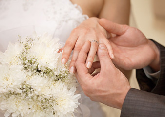 Hands of groom and bride with ring close up