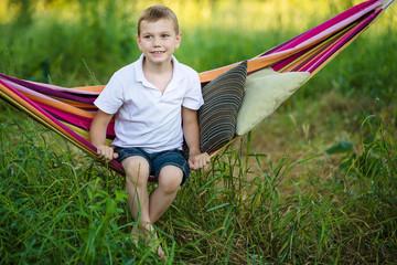 A boy sits in striped hammock in the garden