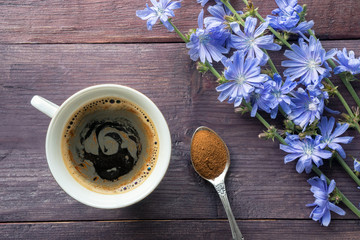 Chicory herbal drink and blue flowers on wooden table. Spoon with root powder. Top view