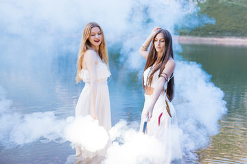 Two young girls having fun into a lake and dancing with flares.