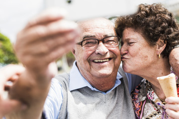 Portrait of smiling senior man taking selfie with his wife