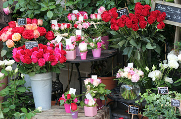 Many bouquets of roses on the sidewalk near a flower shop in Paris.