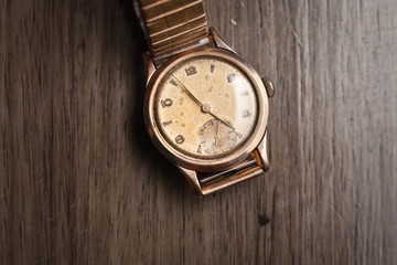 Vintage wristwatch on a wooden table. Classic men's watch