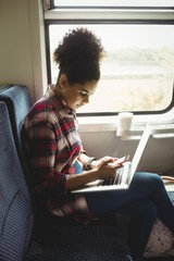 Side view of woman using phone with laptop in train