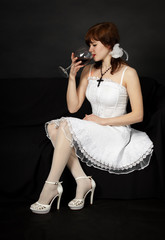 Young beautiful girl sits with a glass
