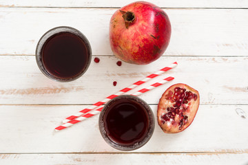 Pomegranate juice on white wooden table background