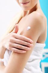 Obraz Nawilżanie przesuszonej skóry. Kobieta wciera w skórę balsam  - fototapety do salonu