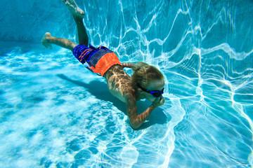 little boy swimming diving underwater