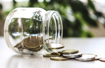 The concept of saving money . The money is scattered from a glass jar on the table.