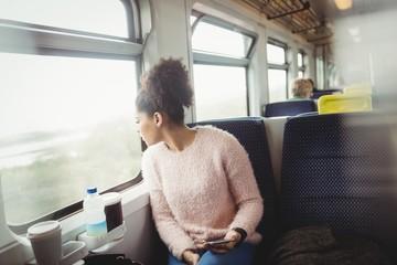 Woman looking through window in train
