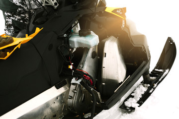 Driver repairing a broken snowmobile. Winter sports.
