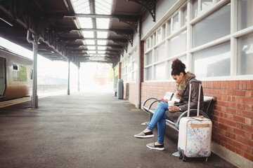 Young woman using phone at railway station