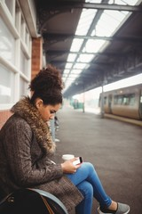 Woman using phone at train station