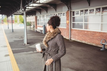 Woman holding disposable coffee cup at railroad station platform