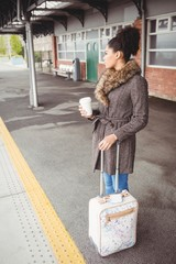 Woman holding disposable coffee cup at railway station platform