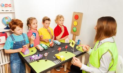 Happy kids teaching traffic signs in kindergarten