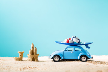 Miniature blue car with surfboard