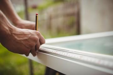 carpenter's hands measuring a door frame