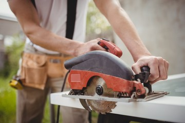 Carpenter cutting wooden frame from circular saw