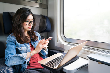 Cute Asian woman using smartphone and laptop on train, copy space on window, business travel or technology concept