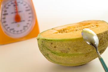 Melone tagliato con cucchiaino e bilancia su sfondo bianco. Cibo sano e dietetico per il controllo del peso.