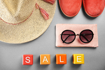 Red shoes, straw hat and sunglasses on grey background. Sale concept