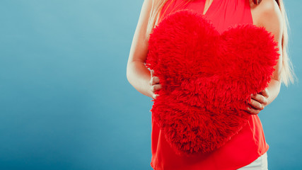 Heart shape pillow in hands. Valentines day love