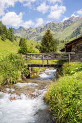 vertical mountain panorama with a wooden bridge on a creek - Pon