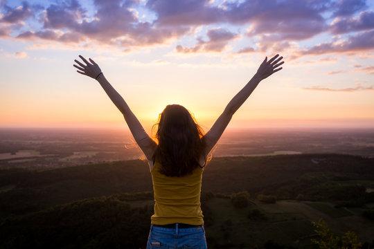 une jeune femme de dos , levant les bras face à un paysage sous le coucher de soleil
