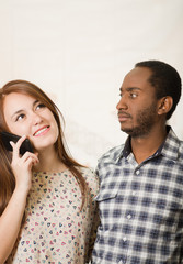 Interracial charming couple wearing casual clothes posing interacting friendly, woman talking on cell phone and man listening in, white studio background