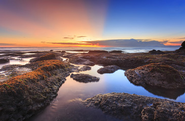 Beautiful vibrant seascape at sunset of Tanah Lot beach in bali, indonesia