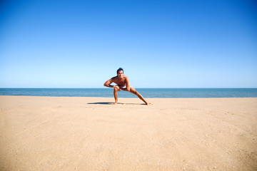 Young shirtless man stretching on the beach