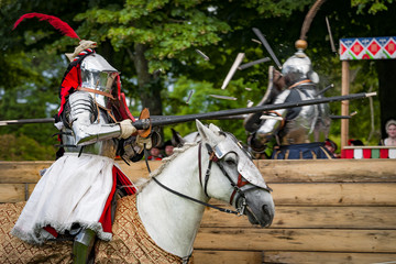 Armored knights on horseback charging in a joust right after the impact . Jousting is a martial game or hastilude between two horsemen wielding lances with blunted tips, often as part of a tournament. Wall mural