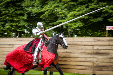 Armored knight on horseback charging in a joust with the lance raised. Jousting is a martial game or hastilude between two horsemen wielding lances with blunted tips, often as part of a tournament Wall mural