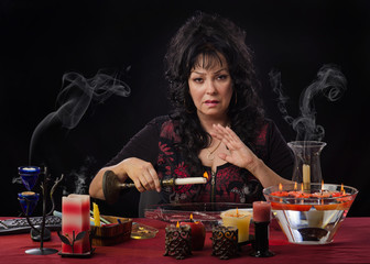 Fortuneteller drips candle wax into water