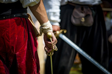 Closeup on the hand holding a sword of a pirate or medieval warrior, preparing to duel another man, there is a bandage on his wrist and the man in the background is blurry