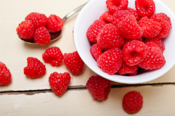 bunch of fresh raspberry on a bowl and white table