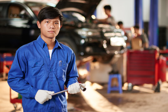 Portrait of young Vietnamese repairman with wrench