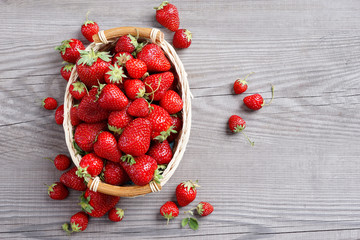 Deluxe strawberries in basket on wooden table. Close up, top view, high resolution product