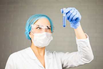 female medical or scientific researcher with a test tube of clear solution in laboratory