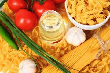 Wall Mural - Different types of raw Italian pasta with tomatoes and other vegetables. Top view background.