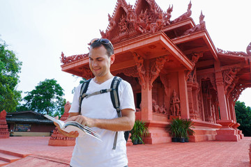 Young male traveler reading guide book at buddhist temple.