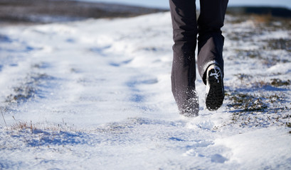 The legs of a hiker walking through a snow covered winter landsc